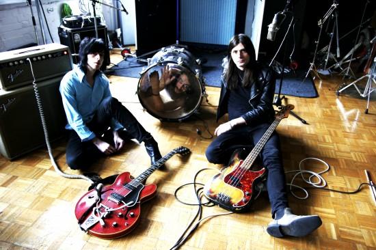 Die Band sitzt auf dem Boden.