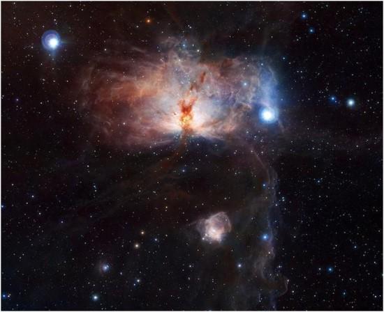 """Der Flammen-Nebel im Orion. Das Infrarotbild zeigt sehr gut die wirre, dreidimensionale Struktur der Wolken, mit einer Brücke aus """"gelbem"""" Gas vor dem leuchtenden Herz des Nebels. Der Pferdekopfnebel ist unten am Bildrand sichtbar, Sigma Orionis ist nur knapp außerhalb des Bildes rechts unten."""